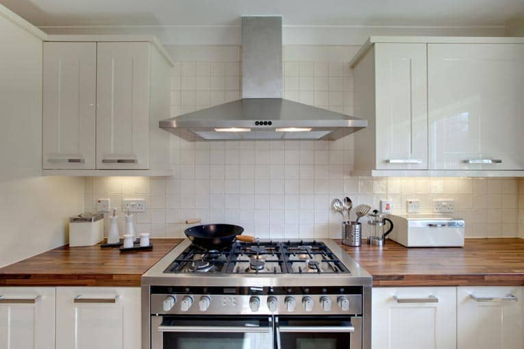 Stainless-steel range hood ventilates commercial-sized gas stove. This unit includes low-voltage lighting.