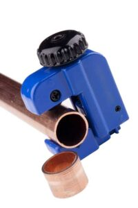 A small blue tubing cutter on a copper pipe with a cutting.