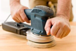 Man's hands sanding a wooden surface with an orbital sander.
