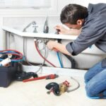 Man installing water supply lines to bathtub valves.