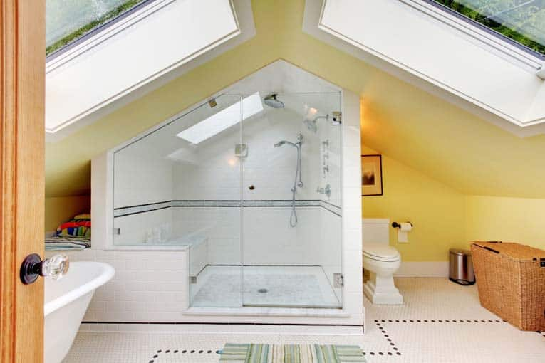 An attic tub and shower bathroom, brightened by two large skylights.