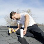 Man sealing a roof vent pipe flashing using a caulk gun.