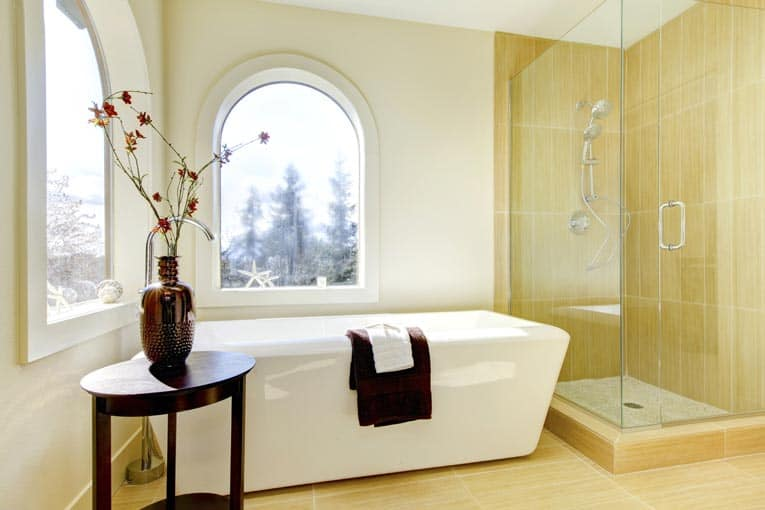 Bathroom with an enclosed glass shower area beside a freestanding tub.