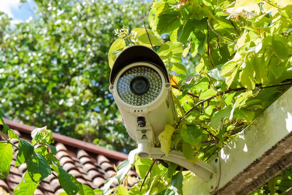 A white bullet-type, outdoor home surveillance camera.