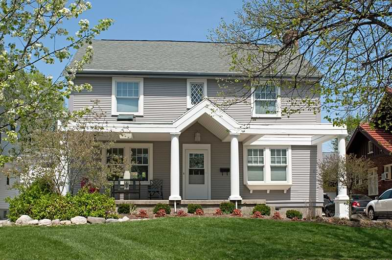 A white and grey suburban home with lush front lawn and trees.