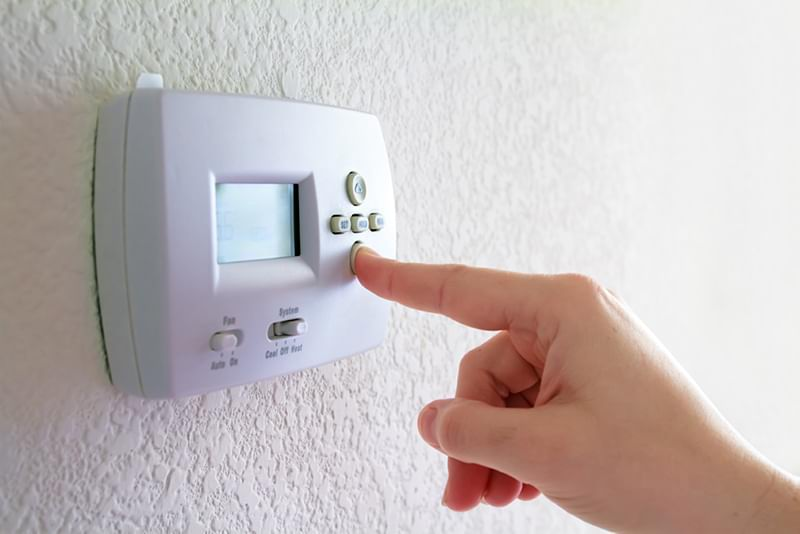 Finger pressing the down button on a programmable thermostat.
