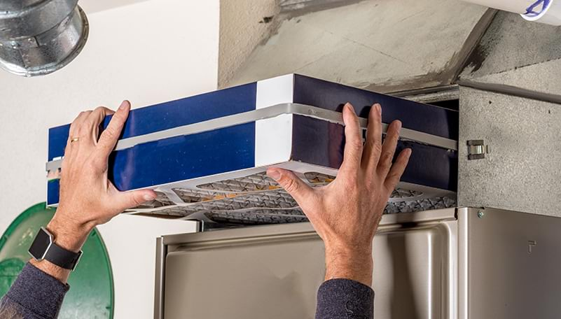 Man's hands changing a furnace filter.