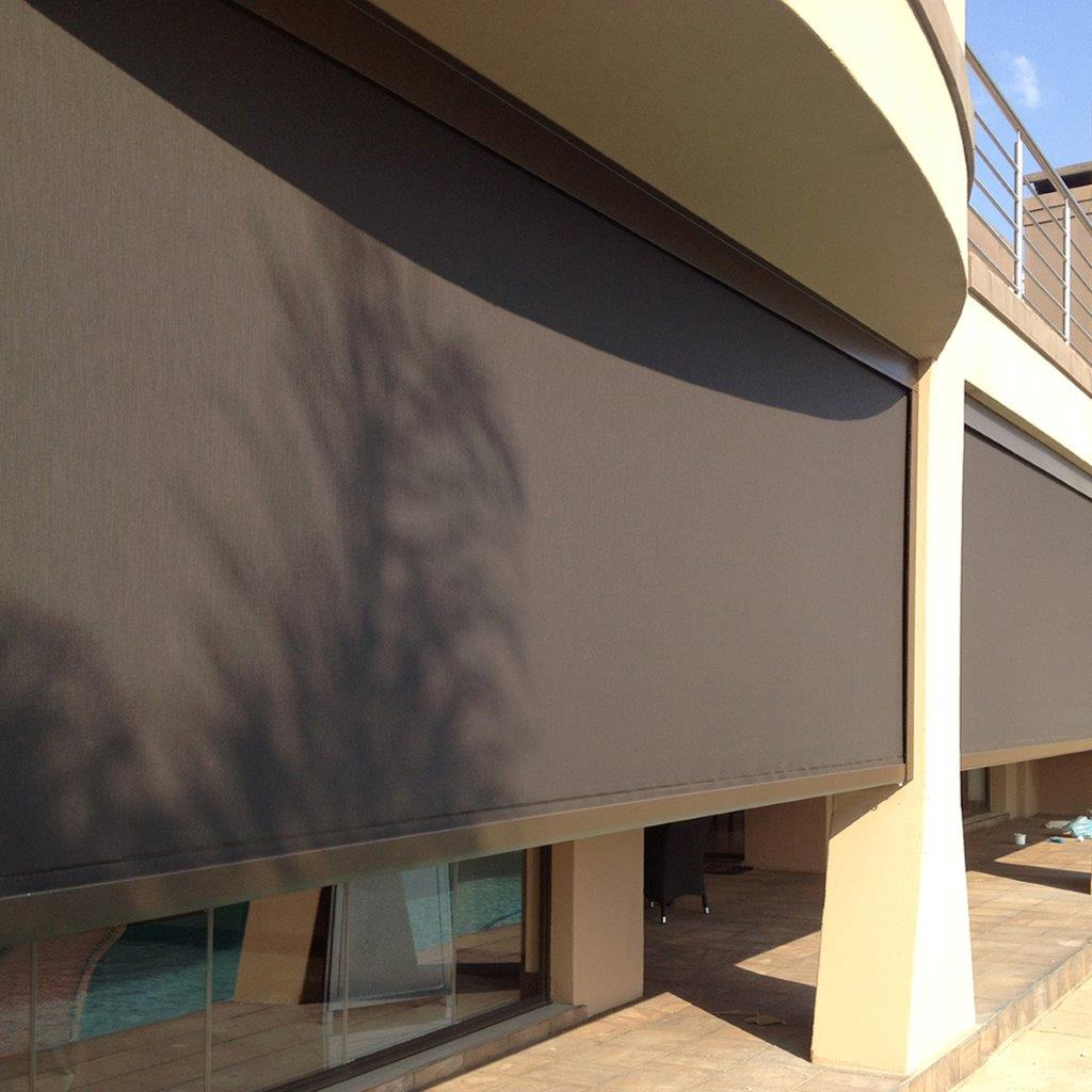 A large exterior solar screen shade with side channel mounts.