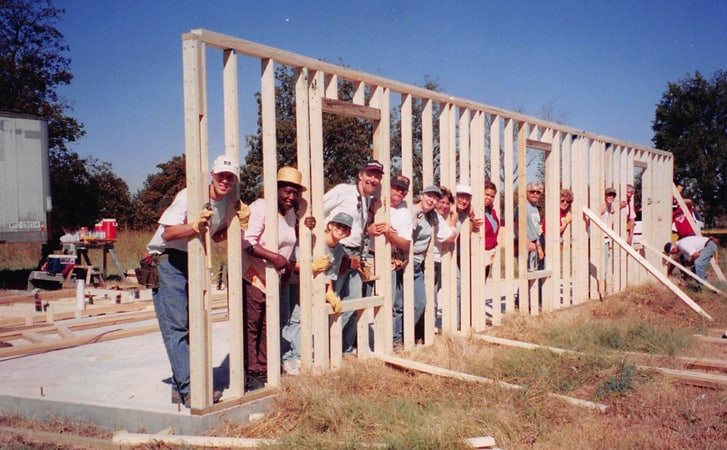 team raising new wall on a concrete slab