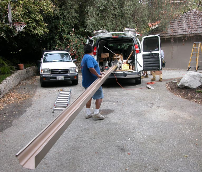 Man supporting a long gutter from an extrusion machine in a van.
