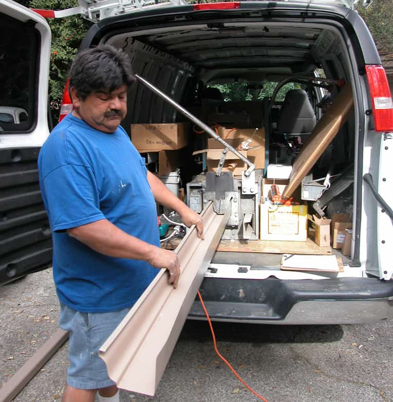 Man holding an aluminum gutter from an extrusion machine in a van.