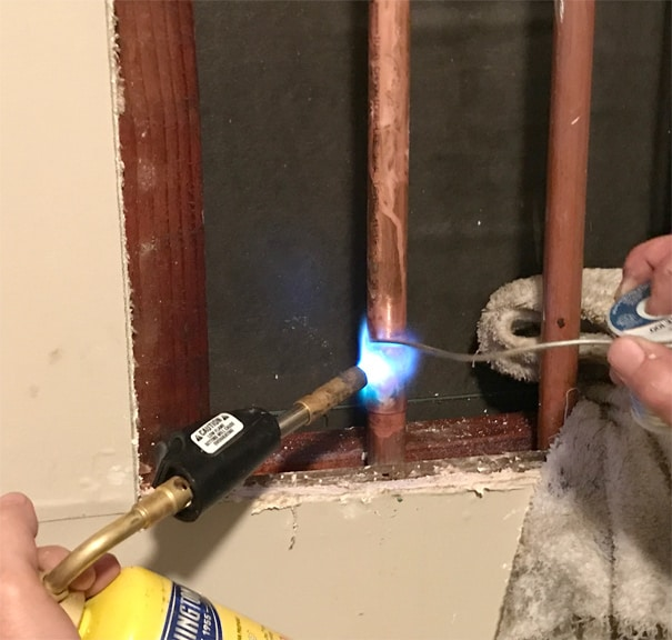 Man's hands soldering a bottom coupling with a Worthington torch kit.