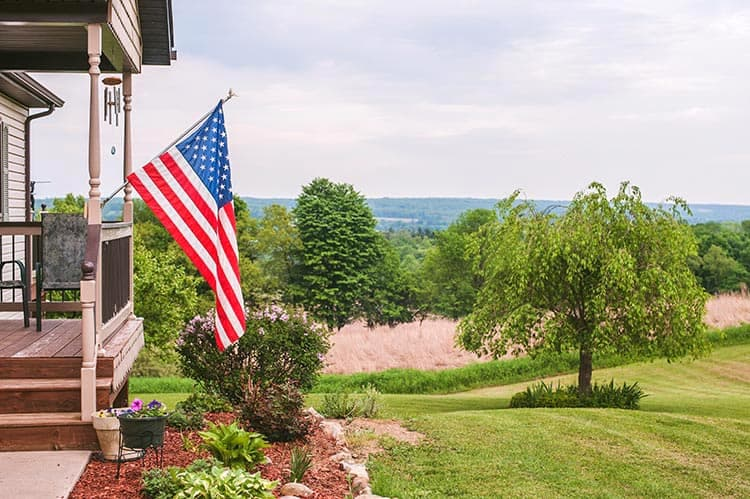 An American flag hung on a house's porch including a front yard.