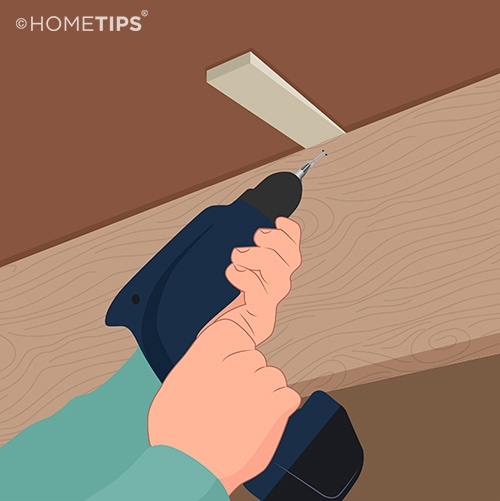 Hands using a power drill to drive a screw through a joist and into a wood shim beneath the floor.