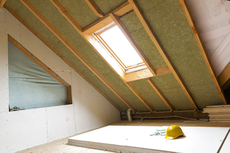 Attic rafters filled with green batt insulation.