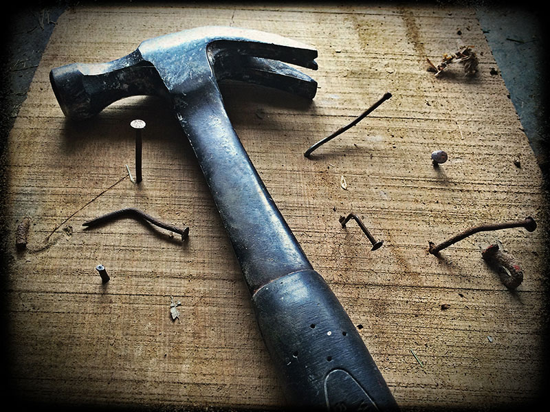 Black claw hammer lying with several bent nails.