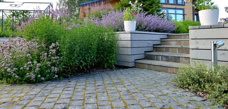 Cobblestones driveway and flagstone stairs surrounded by a vibrant garden.