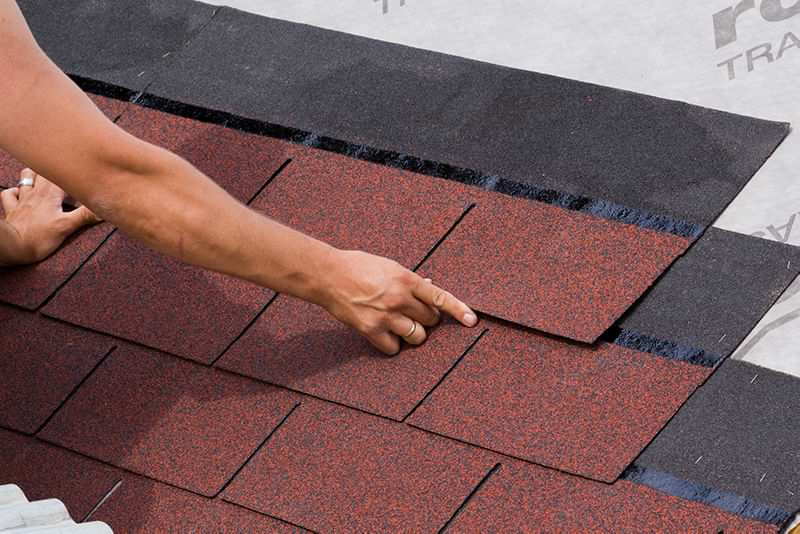 Hands laying a row of staggered asphalt shingles over previous rows.