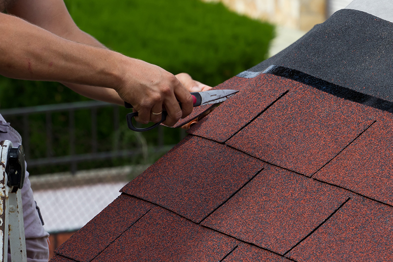 Hands using heavy duty scissors to trim new asphalt shingles at the edge of a roof.
