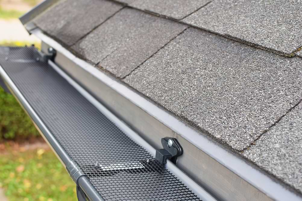 Asphalt roofing tiles and a gutter with a mesh gutter guard on top