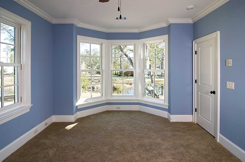 Blue carpeted room with baseboard and crown molding interior trim.